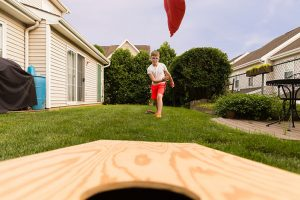 kid playing cornhole in backyard