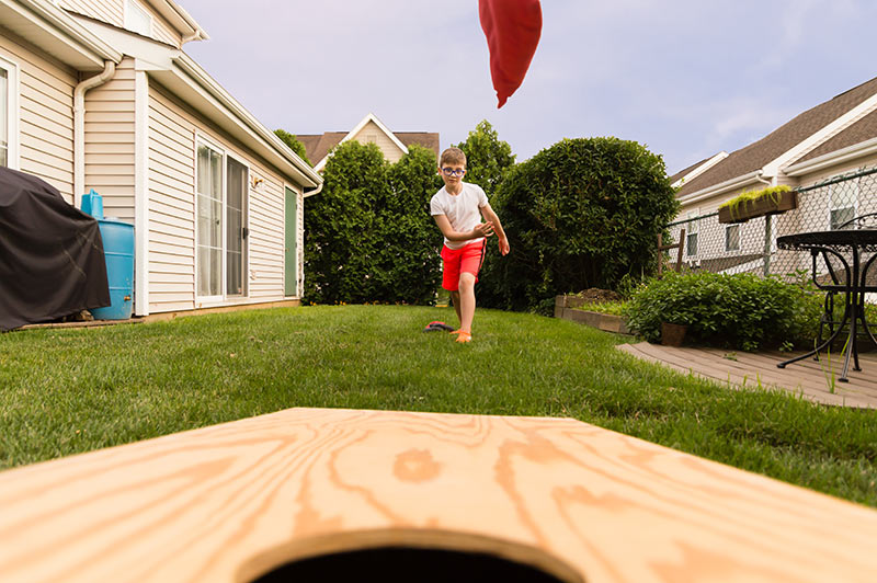 kid playing cornhole in backyard
